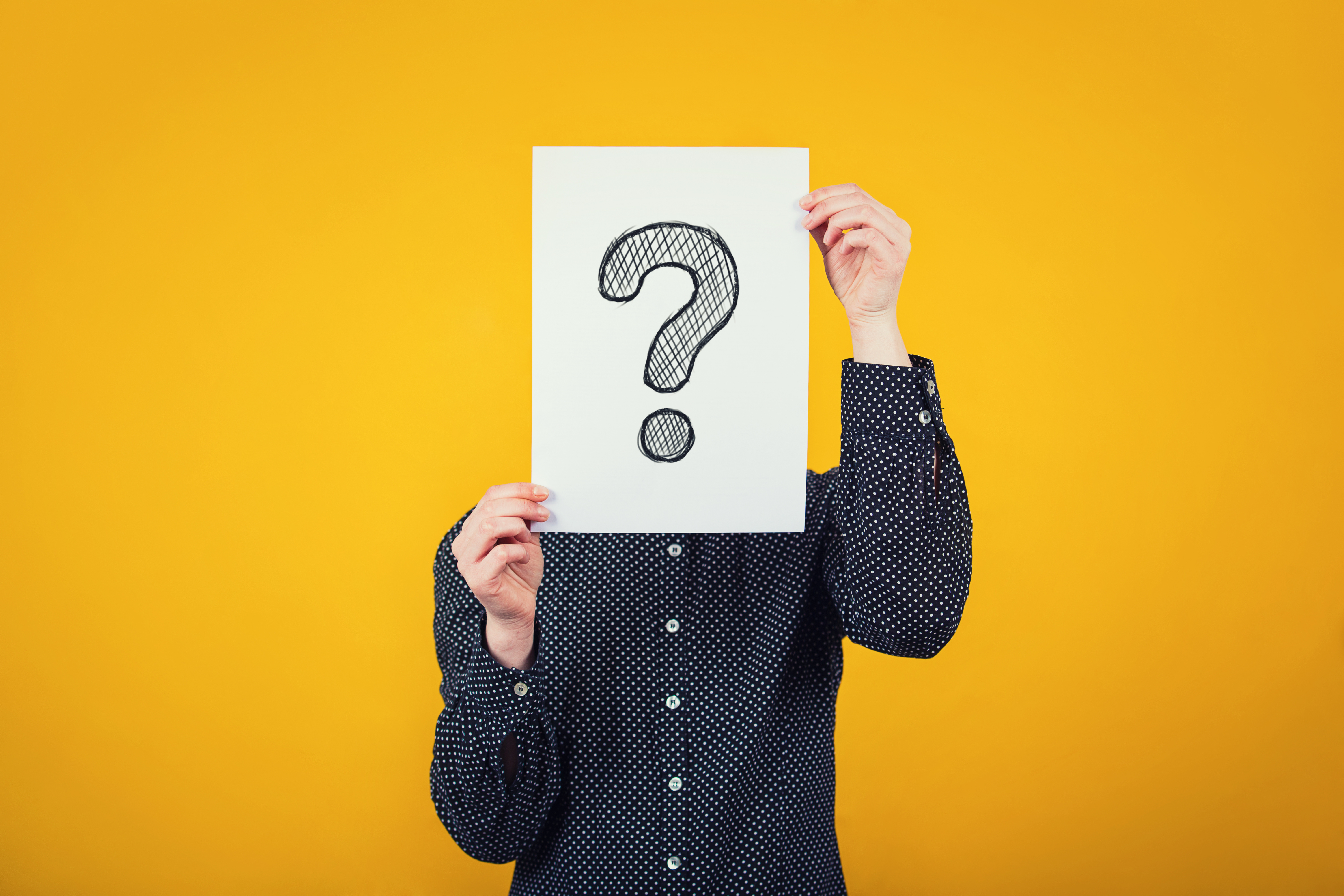 Businesswoman covering face using a white paper sheet with drawn question mark, like a mask, for hiding her identity. Isolated on yellow wall background